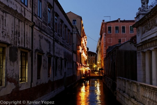 An empty canal at night, with reflected light from lanterns, Venice, Italy