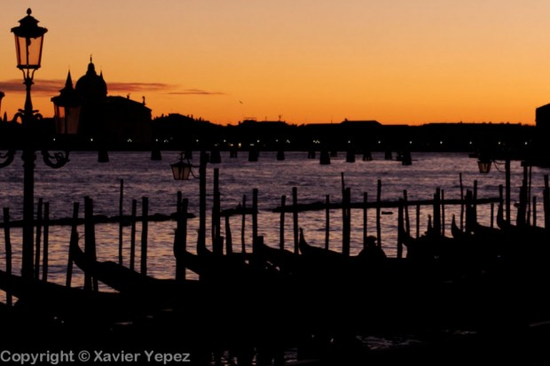 Silhouettes of gondolas against a sunset, Venice, Italy