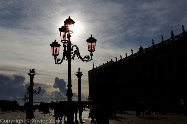 Silhouettes of lanterns against the sun in Piazza San Marco, Venice, Italy