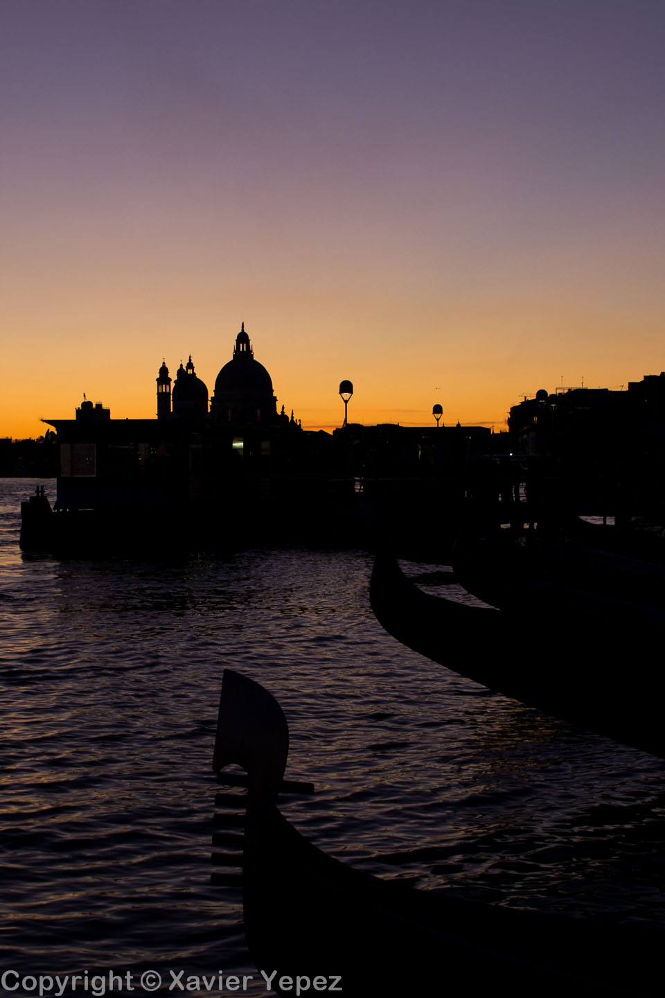 Silhouettes of gondolas and a church in a sunset in Venice, Italy