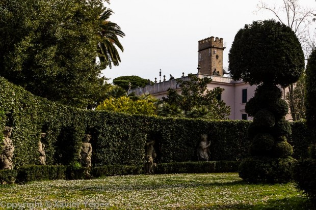 Statues surrounded by hedges, with Villa Sciarra in the background